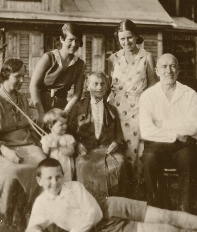 """Šlapelių šeima savo vasarnamyje Valakampiuose, 1932 m. Antroje pusėje Marijos Šlapelienės ranka juodu rašalu užrašyta: """"Šlapeliai – 1932 m. Vilniuje – vasarą savo vasarnamyje –Valakampiuose… Mylimajai Gražutei ir – Aloyzui – naujam bute – daug daug linkėjimų – stiprių sveikatų – sėkmės – laimingiems linksmai – gyventi! Gražutei – po 40 m. prisiminimui. – Karštai mylinti – su laiminimais – Vilniuje 1972.VI.1 d. Nuo visų čia artimųjų – irgi daug linkėjimų…"""" apačioje M. Šlapelienės parašas."""
