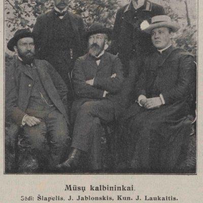 """Nuotrauka """"Mūsų kalbininkai"""" iš 1909 m. leidinio. Sėdi: (iš kairės) J. Šlapelis, J. Jablonskis, Kun. J. Laukaitis. Stovi: Stud. K. Būga, Stud. J. Balčikonis. Apačioje prierašas: """"Šią vasarą mūsų kalbos žinovai susirinkę Seinuose per keletą savaičių svarstė kalbos dalykus. Neužilgo susilauksime naujos gramatikos ir sintaksio. Kalbininkai, apsvarstę didžiuosius dalykus, šiaip išsidalino darbą: Prof. J. Jablonskis rašo sintaksį, Dr. J. Šlapelis – gramatiką, o K. Būga išleis veikalą apie rašybą."""""""