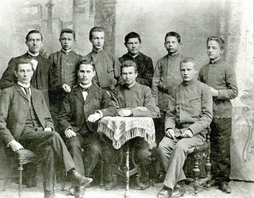 """Mintaujos gimnazistai, 1896 m. Stovi: pirmas iš keirės – Jurgis Šlapelis. Sėdi: antras iš kairės – Antanas Smetona. Jurgiui Šlapeliui mokslas sekėsi labai gerai, klasėje būdavo pirmasis mokinys. Mokėsi kartu su Antanu Smetona. Su juo ir kitais gimnazistais 1896 m. atsisakė melstis rusiškai, dėl to su būreliu draugų buvo išvarytas iš gimnazijos ir vietoj brandos atestato gavo """"vilko bilietą"""" – buvo pašalintas be teisės grįžti ar net stoti į kitą gimnaziją savo krašte. Vėliau Maskvoje eksternu išlaikė brandos egzaminus ir įstojo į Maskvos universiteto Medicinos fakultetą."""