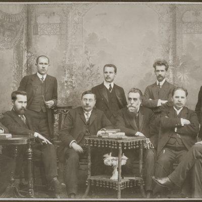 Lietuvių mokslo draugijos komitetas. 1911–1912 m. Sėdi, iš kairės: Juozas Kairiūkštis, Antanas Smetona, prof. August Robert Niemi, Jonas Basanavičius, Antanas Vileišis ir Jonas Vileišis. Stovi, iš kairės: Juozas Balčikonis, Zigmas Žemaitis, Mykolas Biržiška, Jurgis Šlapelis. Antroje nuotraukos pusėje Marijos Šlapelienės visos pavardės užrašytos pieštuku, aukščiau – dar kartą juodu rašalu. Lietuvių mokslo draugija veikė 1907 – 1940 m. ir buvo viena reikšmingiausių kultūros, švietimo ir mokslo organizacijų Vilniaus krašte. Lietuvių mokslo draugiją kartu su bendraminčiais 1907 m.įsteigė daktaras Jonas Basanavičius Steigimo metais Mokslo draugijoje buvo 156 nariai, tarp jų ir Jurgis Šlapelis. Iš viso per draugijos gyvavimą jos veikloje dalyvavo apie 1,5 tūkst. žmonių. Draugijos nariai formavo tautos ir būsimosios Lietuvos valstybės ateitį, jų veikla bei pastangos lietuvių tautą išvedė į Nepriklausomybės siekimo kelią. Pradėta nuo paprastų, bet esminių dalykų: mokyklų visoje šalyje steigimo, lietuviškų vadovėlių ir knygų leidybos. Iš Lietuvių mokslo draugijos veiklos išsirutuliavo Lietuvos valstybingumo idėja. Iš 20-ies 1918 m. Vasario 16-osios Nepriklausomybės aktą pasirašiusių signatarų net 19 buvo Lietuvių mokslo draugijos nariai. Taip pat trys būsimieji Lietuvos prezidentai – Aleksandras Stulginskis, Kazys Grinius ir Antanas Smetona, du ministrai pirmininkai – Augustinas Voldemaras ir Juozas Tūbelis buvo draugijos nariai.