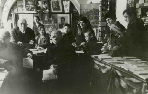 """Marijos ir Jurgio Šlapelių knygyne. 1931 m. Nuotraukoje antras iš kairės – Jurgis Šlapelis, šalia sėdi Marija Šlapelienė, toliau – jų sūnus Skaistutis. 1906 m. Marijos ir Jurgio Šlapelių Vilniuje, Dominikonų gatvėje, atidarytas lietuvių knygynas buvo vienas pirmųjų ir ilgiausiai, per visas penkias Vilniaus okupacijas, daugiaus nei 40 metų nenutrūkstamai veikęs ir profesionaliai tvarkytas knygynas, ilgą laiką dominavęs knygų rinkoje. Labai svarbų veiklos barą – knygų leidybą, knygynas pradėjo 1907 m. Pirmoji išleista Gabrieliaus Landsbergio-Žemkalnio melodrama """"Birutė"""". Knygyno veikla ir bet kokia leidyba užsibaigė po Antrojo pasaulinio karo. Sovietų valdžia 1949 m. pareikalauja skubiai atlaisvinti knygyno patalpas. Vidaus reikalų ministerijos nurodymu Lietuvos knygų rūmai be jokio atlygio perima M. Šlapelienės knygyno likučius. Po kelerių metų buvo paskelbta, kad Knygų rūmai perėmė iš Šlapelių knygyno apie 10 tūkst. leidinių. Dėl šių gautų knygų ir kitų leidinių Knygų rūmai tapo viena didžiausių senosios spaudos saugyklų Lietuvoje. Šlapelių šeimos ir knygyno arcyvas svarbus šaltinis kultūros, knygos bei knygininkystės istorijai."""
