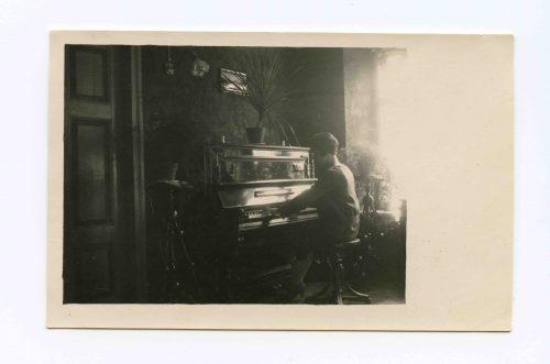 Gražutė Šlapelytė skambina pianinu savo namuose Pilies g. 1928 m. Marija Piaseckaitė-Šlapelienė šį Muhlbach firmos pianiną įsigijo būdama dar 18-likos. Jis stovėjo šeimos namuose Saracėnų gatvėje (1926 m. Šlapeliai persikėlė į namą Pilies g. 40), kur pas Jurgį Šlapelį pasimokyti lietuvių kalbos ateidavo įvairaus amžiaus vilniečių. Tarp besimokančiųjų buvo ir Mikalojus Konstantinas Čiurlionis, kuris mėgdavo prisėsti ir paskambinti šiuo pianinu. Juo taip pat pagrodavo artimas Šlapelių šeimos draugas kompozitorius Mikas Petrauskas.