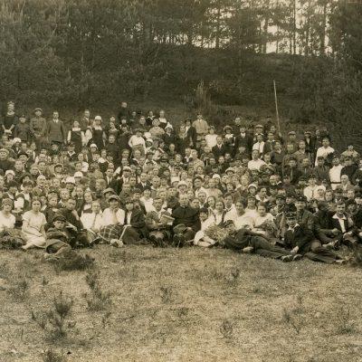 Gimnazistų ir pedagogų (Vytauto Didžiojo gimnazijos) iškyla, 1926 m. Pulkas moksleivių su mokytojais pievoje prie miško. Pirmoje eil. iš kair. 4-ta sėdi Laimutė Šlapelytė, tiesiai už jos sėdi Jurgis Šlapelis, centre, už jaunuolio su laikraščiu rankoje sėdi Gražutė Šlapelytė (su balta palaidine ir juoda kepurėle),pirmoje eilėje, centre sėdi kun. Kristupas Čibiras, paskutinėje eil. deš. stovi kun. Pranas Bieliauskas.