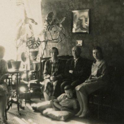 Šlapelių šeima savo namuose Pilies g. 1929 m. Fotografas Aleksandras Jurašaitis. Iš kairės ant kėdės sėdi dukra Gražutė, ant sofos – Marija Šlapelienė, Jurgis Šlapelis, dukra Laimutė, jiems prie kojų – sūnus Skaistutis.