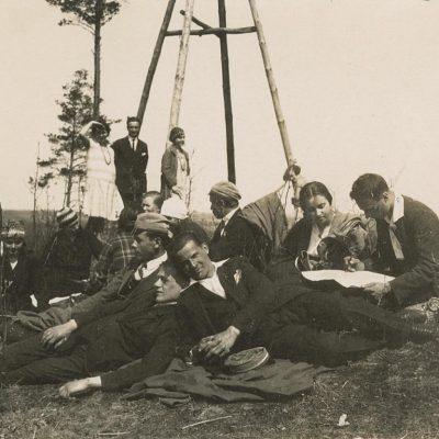 """Vilniaus studentų iškyla, 1928 m. Tarp kitų studentų antrame plane stovi Laimutė (kairėje) ir Gražutė (dešinėje) Šlapelytės. Antroje pusėje Gražutės užrašas juodu rašalu: """"Vilniaus studenterija džiaugiasi pavasariu. 1928-V-6 d.""""."""