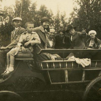 """Jurgis, Laimutė, Gražutė ir Skaistutis Šlapeliai """"bričkoje"""", 1930 (?) m. Iš dešinės: pirmas – Jurgis Šlapelis, penkta – Laimutė Šlapelytė-Graužinienė, šalia jos – Gražutė Šlapelytė ir Skaistutis. Antroje nuotraukos pusėje kažkieno violetiniu pieštuku sunkiai įskaitomu raštu užrašyta: """"Laimute, ačiū už laiškutį – parašysiu, kaip būsi Vilniuje, o dabar – ant visi linkėjimai""""."""