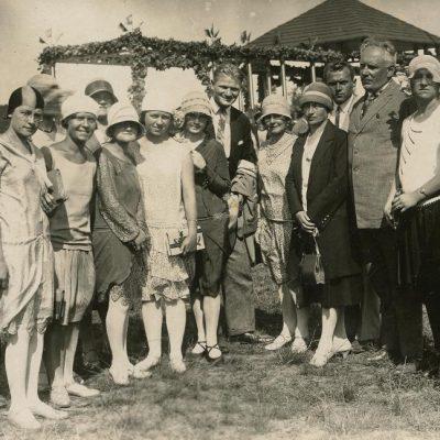 """Vilniečiai po iškilmių Kaune, 1929 m. Fotografas E. Dryža. Iš kairės trečia stovi Gražutė Šlapelytė, penkta – jos sesuo Laimutė Graužinienė. Antroje nuotraukos pusėje violetiniu rašalu ovaliu spaudu atspausta fotografo pavardė ir adresas: """"E. Dryža / Šančiai / IV kranto g. 1"""". Taip pat juodu rašalu užrašyta: """"Vilniečiai 1929 rugpjūčio m. 15 d. parado aikštėje po iškilmių / Kaunas""""."""
