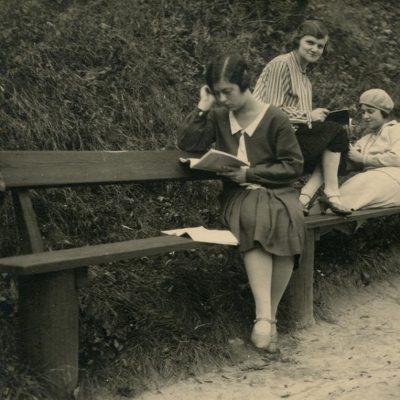 """Gražutė ir Laimutė Šlapelytės su drauge mokosi Gedimino kalno papėdėje. 1928 m. Universiteto studentės ruošiasi paskaitoms: pirma iš kairės sėdi Gražutė, antra – E. Valterytė, trečia – Laimutė Šlapelytė. Antroje pusėje užrašyta juodu rašalu: """"Ne vieną ir ne dešimt kartų mūsų čia zubrinta / Vilnius, Gedimino kalnas 1928-X-22d."""""""