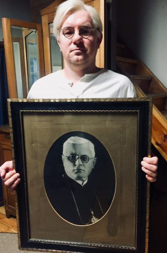 """Aktorius R. Cicėnas filmuojant dokumentinį filmą """"Tumo kodeksas"""". Rankose laiko Vaižganto portretą, kuris kabėjo Šlapelių namuose, o dabar puošia muziejų ir primena apie artimą kunigo draugystę su Šlapeliais."""