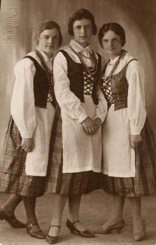 Trys tautiniais rūbais pasipuošusios merginos: viduryje Laimutė Šlapelytė, dešinėje – Liusia Valterytė, dešinėje – Marytė Čenytė. 1928-ieji - atkurtos Lietuvos valstybės dešimtmetis.