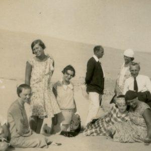 """Šlapelių vaikai ir K. Graužinis su draugija Nidos kopose. 1929 m. Gražutė (stovi kairėje), Laimutė (stovi dešinėje) ir Skaistutis (sėdi pirmas iš kairės). Šalia Laimutės stovi jos būsimasis sutuoktinis Kazys Graužinis. Kitoje nuotraukos pusėje Gražutės ranka juodu rašalu užrašyta: """"Tra lia-lia! / Nida 1929-VIII-11d."""""""