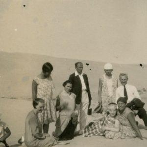 """Šlapelių vaikai su draugija Nidos kopose. 1929 m. Gražutė (stovi kairėje), Laimutė (stovi dešinėje) ir Skaistutis (sėdi pirmas iš kairės). Šalia Laimutės stovi jos būsimasis sutuoktinis Kazys Graužinis. Kitoje nuotraukos pusėje Gražutės ranka juodu rašalu užrašyta: """"Lietuvos Sacharoje / Nida 1929-VIII-11d."""""""