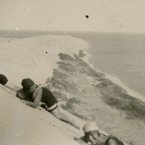 """Marija Šlapelienė Nidos kopose su savo vaikais. 1929 m. Marija Šlapelienė (viduryje) ir jos vaikai – duktė Gražutė ir sūnus Skaistutis. Kitoje nuotraukos pusėje Gražutės ranka juodu rašalu užrašyta: """"Tai bent gyvenimas!/ 1929-VIII-11d./ Nida""""."""