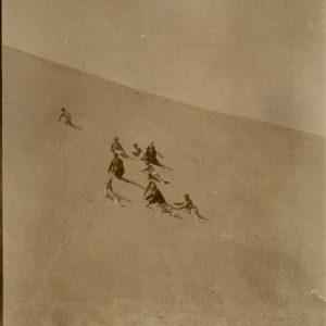 Šlapeliai su kompanija lipa į Nidos kopą. 1929 m. rugpjūčio 11 d. Ta Draugija nufotografuota iš toli, besivoliojanti kopų smėlyje. Žemiausiai per vidurį, baltomis kelnėmis – diplomatas Kazys Graužinis, už jo – sužadėtinė Laimutė Šlapelytė, už 9 dienų tapsianti jo žmona. Kairėje, aukščiausiai į kopą įsiropštęs – Skaistutis Šlapelis.