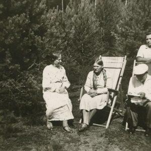 Šlapeliai su sūnum Skaistučiu ir viešnia savo vasarnamyje Valakampiuose. 1932 m. Šlapeliai dažnai vasarodavo savo viloje už miesto, Valakampiuose. Iš kairės sėdi Marija Šlapelienė, šalia jos – viešnia, iš dešinės – Jurgis Šlapelis. Virš jo stovi sūnus Skaistutis.