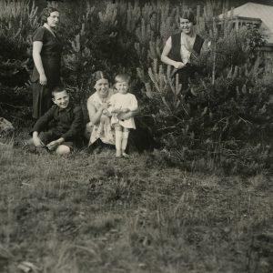 Laimutė Graužinienė su dukrele vieši tėvų viloje Valakampiuose. 1932 m. Pirma iš dešinės stovi Gražutė Šlapelytė, tupi jos sesuo Laimutė, apkabinusi dukrelę Laimutę, šalia ant žolės sėdi Skaistutis. Stovi nežinoma Šlapelyčių draugė.