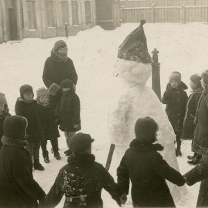 """Vaikai su mokytoja džiaugiasi žiemos malonumais. 1930 m. Vilnius. Antroje nuotraukos pusėje užrašyta juodu rašalu: """"Vaikučiai su mokytoja Tamulevičiūte iš """"Kultūros"""" mokyklos Vilniuje"""" ir mėlynu rašalu – """"čia – gal yra – ir – Mieliausias sūnelis – Skaistutis""""."""