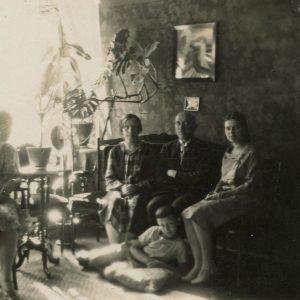 """Šlapelių šeima savo namuose Pilies g. 1929 m. Fotografas Aleksandras Jurašaitis. Visa Šlapelių šeima savo namų svetainėje: iš kairės ant kėdės sėdi dukra Gražutė, ant sofos – Marija Šlapelienė, Jurgis Šlapelis, dukra Laimutė, jiems prie kojų – sūnus Skaistutis. Antroje fotografijos pusėje M. Šlapelienės užrašas juodu rašalu – """"Mūsų salione, 1929-VII, Vilnius""""."""