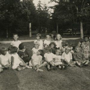 """Skaistutis tarp vaikų. 1929 m. Skaistutis – Šlapelių jaunėlis – paskutinėje eil. pirmas iš kairės. Ant rėmelio aplink nuotrauką Marijos Šlapelienės aprašyta juodu ir mėlynu rašalu: """"Laimutės – atsiųsta nuotr. 1929 m. Mano mieliausias Skaistutis – stovi pirmas iš kairės – Jam 10 m."""". Antroje nuotraukos pusėje ilgas Laimutės laiškelis broliui Skaistučiui, rašytas 1929.XI.25."""