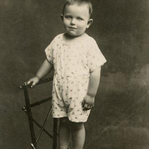 """Skaistutis stovi ant kėdės. 1921 m. Antroje nuotraukos pusėje Marijos Šlapelienės ranka užrašyta mėlynu rašalu: """"Mylimiausias sūnelis Tutis / 1919.V. – 1961.IV.8 d.""""."""