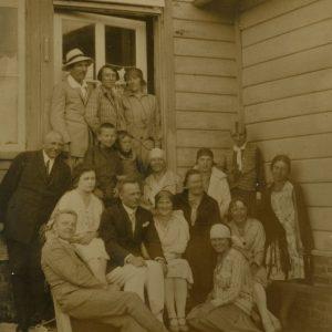 """Grupė žmonių ir Šlapelių vaikai prie Žaliosios vilos Palangoje. 1928 m. Didelėje grupėje poilsiautojų yra visi Šlapelių vaikai: pirma iš dešinės sėdi ant žemės Laimutė, trečioje eilėje pirma iš dešinės stovi Gražutė, antras iš kairės – Skaistutis. Kitoje pusėje pieštuku užrašyta: """"Žaliosios vilos šeimynėlė (+ du simpatiku) / Palanga / 1928-VII-19d."""""""