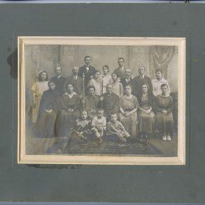 """Jono ir Eleonoros Piaseckų auksinės vestuvės. Visa giminė. 1923 m. Centre sėdi Marijos tėvai – Jonas ir Eleonora Piaseckai. Iš dešinės tėvui – pati Marija Šlapelienė. Šalia jos – brolio Stasio žmona, virš jos – vyras Stasys Piaseckas. Iš kairės Eleonorai Piaseckienei sėdi dvi jos dukros – Halina ir Jadvyga, virš jų stovi abiejų vyrai – Riauba ir Klišeika. Virš Piaseckų šviesiai apsirengusios stovi abi Šlapelytės – Laimutė ir Gražutė. Šalia Gražutės stovi Jurgis Šlapelis. Ant grindų viduryje sėdi Šlapelių sūnus Skaistutis. Visi kiti – Piaseckų anūkai, sūnų ir dukterų vaikai. Antroje nuotraukos pusėje Marijos Šlapelienės juodu rašalu užrašyta: """"Jono ir Eleonoros Piaseckių Aukso jungt. 1923 m. 23. IX. / Jungt. buvo 1873. 23. IX / Mano tėvelių (prie tėvelio sėdžiu aš, viršuje – prie manęs stovi mano vyras daktaras Jurgis Šlapelis)."""" Toliau išvardinti visi nuotraukoje esantys artimieji. Paskutinė eilutė: """"Trūksta – brolio Petro ir jo žmonos ir brolio Stasio dukrelės (buvo ji 2-jų metų)""""."""