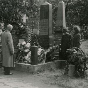"""Skaistutis Šlapelis su grupe prie Jono Basanavičiaus kapo. 1939 m. Šioje nuotraukoje Skaistučiui Šlapeliui 20 metų. Skaistutis (stovi toliausiai kairiame kampe) su grupe atėjo į Rasų kapines, prie Jono Basanavičiaus kapo. Kitoje nuotraukos pusėje jo ranka pieštuku užrašyta: """"1939 m. Sekminės. K! Romuva Vilniuj"""". Marijos Šlapelienės ranka užrašyta: """"Jo rankele – užrašyta / čia yra – nuliūdusiu veidu Jis – pats ekskurs. vadovas."""""""