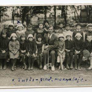 """Skaistutis Šlapelis – mokinukas. 1926 (?) m. Fotografas nežinomas. Skaistutis su pradinės mokyklos klasės draugais ir mokytoju. Skaistutis stovi antroje eilėje ketvirtas iš kairės. Jam virš galvos mėlynu rašalu pažymėtas kryžiukas, apačioje Marijos Šlapelienės ranka parašyta: """"Tutis – prad. mokykloje."""""""