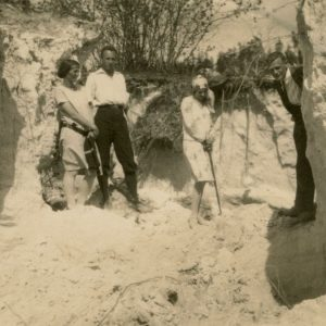 """Gražutė (stovi antra iš dešinės) su trim draugais prie smėlėto skardžio paežerėje. Kitoje nuotraukos pusėje užrašyta: """"Prie Žaliojo ežero 1929-V-26d."""""""