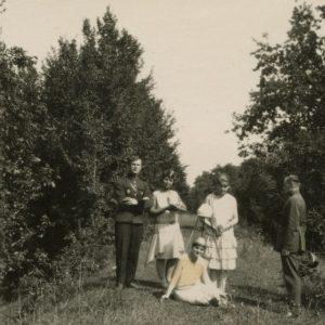 """Gražutė Šlapelytė (stovi kairėje) su dviem draugėmis ir Lietuvos karo lakūnais Aukštojoje Fredoje, Kaune. Kitoje nuotraukos pusėje Gražutės ranka užrašyta: """"Čia tai ne betkokie lakūnai!/ A. Freda 1929-VIII-18d."""""""