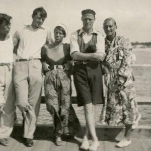 """Gražutė Šlapelytė tarp sportiškos išvaizdos jaunuolių stovi ant Palangos tilto. Kitoje nuotraukos pusėje Gražutės ranka užrašyta: """"Palanga 1932– VIII –""""."""