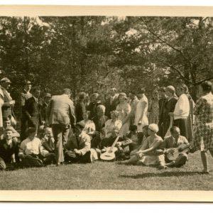 """Studentų ekskursija Verkiuose. 1930 m. Gražutė (sėdi ant žolės antra iš dešinės) su dideliu būriu Vilniaus universiteto studentų. Kitoje pusėje užrašyta: """"Mūsų studenterija ekskursuoja / Verkiai /1930-V-18d."""""""