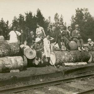 """Grupė studentų nusifotografavo prie geležinkelio. Pirmoje eilėje trečia iš kairės – Laimutė Šlapelytė. Virš jos – sesuo Gražutė. Kitoje nuotraukos pusėje užrašyta juodu rašalu: """"Prie gelželio už tunelio… / 1928-V-6 d."""""""
