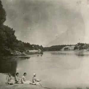 """Keturios merginos sėdi ant smėlėto upės kranto. Gražutė – pirma iš dešinės. Kitoje pusėje Marijos Šlapelienės ranka pieštuku užrašyta: """"Laimingosios – berūpesčių… Sena nuotraukėlė / nei – kur – nei – kas / bet – įdomu"""". 1929 (?) m."""