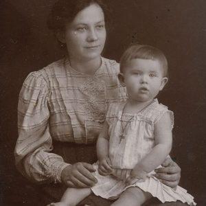 Gražutė Šlapelytė mamai ant kelių, 1911 m. Fotografas Aleksandras Jurašaitis. Gražutė aprengta balta berankove suknyte, jai ant kaklo kabo kryželis, dovanotas jos krikšto tėvo Jono Basanavičiaus.