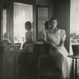 Gražutė Šlapelytė prie veidrodžio savo namuose Vilniuje. 1928 (?) m. Tuo metu jaunesnioji Šlapelių dukra Gražutė studijavo filosofiją, lituanistiką ir polonistiką Stepono Batoro universitete. Mergina sėdi prie veidrodžio, kuris yra išlikęs, jį galima pamatyti memorialinio muziejaus ekspozicijoje.