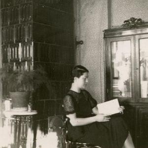 Gražutė Šlapelytė savo kambaryje skaito knygą. 1928 (?) m. Kėdė, ant kurios mergina sėdi, ir spinta stiklinėmis durimis, yra išlikusios ir eksponuojamos memorialiniuose muziejaus kambariuose.