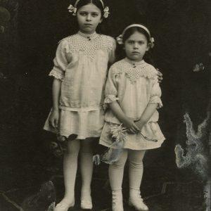 Laimutė ir Gražutė Šlapelytės. 1914 m. Fotografas Aleksandras Jurašaitis. Sesutės stovi aprengtos vienodais baltais drabužėliais, suknelės papuoštos mezginių apykaklėmis, plaukai perjuosti baltais lankeliais su kaspinėliais šonuose, rankose laiko po gėlę.