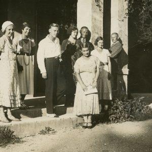 Gražutė vasaroja su draugais. 1928–1929 m. Prie mūrinio pastato grupė draugų. Gražutė stovi antra iš kairės.
