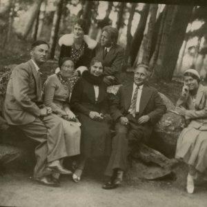 """Palangos parke, prie Birutės kalno, sėdi grupė žmonių. Gražutė Šlapelytė – pirma iš dešinės. Kitoje pusėje jos užrašyta: """"Palanga / 1933-VII-28 d."""""""