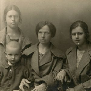 """Marija Šlapelienė su savo vaikais Kaune. Jai iš dešinės sėdi dukra Laimutė, iš kairės – sūnus Skaistutis, už jo stovi dukra Gražutė. Antroje pusėje Šlapelienės užrašyta juodu rašalu – """"Pirmą kartą Nepriklausomojon atsilankius, 1924 m. liepos m., M. Šlapelienė su vaikais Kaune""""."""