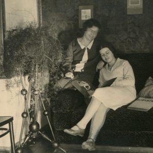 Gražutė ir Laimutė Šlapelytės savo namuose Pilies g. 1928 m. Ant sofos susiglaudusios sėdi abi Šlapelių dukros (iš kairės): Gražutė ir Laimutė, sklaido fotografijų albumą. Fotografuota šeimos svetainėje.