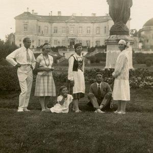 """Laimutė ir Gražutė Šlapelytės Palangoje, Tiškevičių rūmų parke. 1927 m. Iš kairės: stovi Kazimieras Graužinis, tapsiantis Laimutės Šlapelytės vyru, prie Laimutė, toliau – tautiniais rūbais apsirengusi Gražutė Šlapelytė, kiti trys asmenys – nežinomi. Antroje pusėje Gražutės ranka užrašyta: """"Palanga, Tiškevičiaus parke / 1927.VII.31."""""""