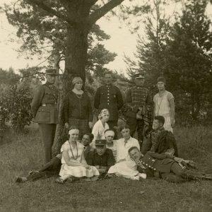 """Laimutė ir Gražutė Šlapelytės karininkų draugijoje Palangoje. Laimutė sėdi pirma iš kairės, Gražutė stovi pirma iš dešinės. Antroje pusėje Gražutės Šlapelytės ranka užrašyta: """"Palanga / simpatiškų karininkų / (ir husarų) draugijoje / 1927.VII.24""""."""