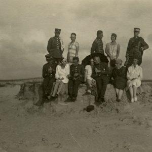 """Gražutė ir Laimutė su draugais Palangos kopose. Ant smėlio kopos antra iš kairės stovi Laimutė, Gražutė – antra iš dešinės. Visi 6 vyrai vilki kariškomis uniformomis. Antroje pusėje Gražutės užrašyta: """"Palangos smėlyje / 1927.VII.24."""""""