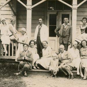 """Prie medinio mokytojų sanatorijos pastato pozuoja grupė jaunimo. Laimutė stovi ketvirta iš kairės, Gražutė – antroje eilėje antra iš dešinės, sėdi ant turėklo, apsirengusi tautiniu kostiumu. Antroje fotografijos pusėje Gražutės užrašyta: """"Palanga, mokytojų sanatorija / 1927.VIII.1."""""""