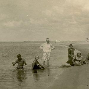 """Laimutė ir Gražutė Šlapelytės Palangos pajūryje. Septyni jaunuoliai pozuoja ant jūros pakrantės. Gražutė – antra iš kairės sėdi vandenyje, Laimutė – trečia iš dešinės, rankose laiko kamuolį. Antroje fotografijos pusėje Gražutės užrašyta: """"Palanga, atsisveikinant / su jūra, 1927.VIII.7."""""""
