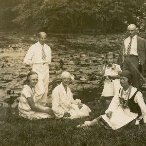 """Šešių žmonių kompanija maloniai leidžia laiką prie vandens lelijomis apaugusio tvenkinio Tiškevičių rūmų parke Palangoje. Pirma iš kairės sėdi Laimutė, prie jos stovi būsimasis vyras Kazimieras Graužinis. Pirma iš dešinės sėdi Gražutė. Antroje pusėje juodu rašalu užrašyta: """"Palanga, Tiškevičiaus / parke, prie prūdo. / 1927.VII.31."""""""
