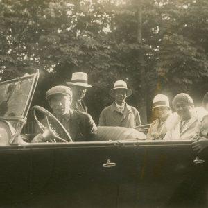 """Šlapelių vaikai automobilyje. Nufotografuoti septyni žmonės, penki iš jų sėdi atvirame automobilyje. Iš dešinės antras – Skaistutis Šlapelis, šalia jo – Gražutė ir Laimutė Šlapelytės. Nuotraukos antrojoje pusėje juodu rašalu užrašyta: """"Gerajai Gražutei / nuo/Negerojo majoro Balsio / 30-VII 1927 m."""""""