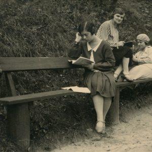 """Šlapelytės su drauge mokosi Gedimino kalno papėdėje. Universiteto studentės ruošiasi paskaitoms: pirma iš kairės sėdi Gražutė, antra – E. Valterytė, trečia – Laimutė Šlapelytė. Antroje pusėje: """"Ne vieną ir ne dešimt kartų mūsų čia zubrinta / Vilnius, Gedimino kalnas 1928-X-22d."""""""